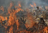 FILE - In this April 29, 2021, file photo, a man runs to escape heat emitting from the multiple funeral pyres of COVID-19 victims at a crematorium in the outskirts of New Delhi, India. India's excess deaths during the pandemic could be a staggering 10 times the official COVID-19 toll, likely making it modern India's worst human tragedy, according to the most comprehensive research yet on the ravages of the virus in the south Asian country. (AP Photo/Amit Sharma, File)