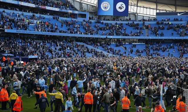 Manchester City fans invade the pitch after the Premier League victory over Swansea, their first home game since being confirmed as champions.