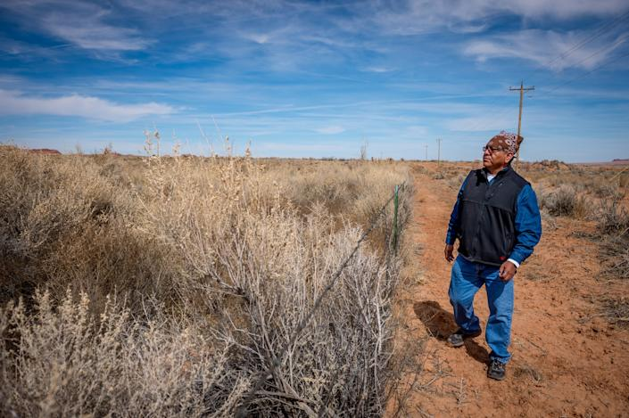 Dariel Yazzie walks along the fence around the covered-uranium tailings pile near his family's house. (Photograph by Mary F. Calvert)