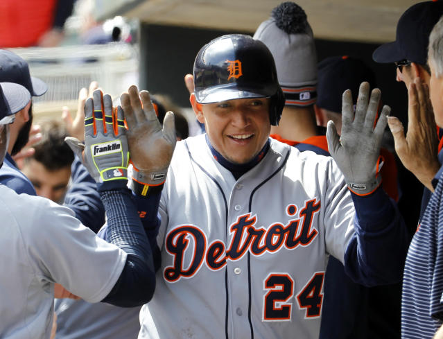 Detroit Tigers' Miguel Cabrera (24) is congratulated by teammates after scoring on a sacrifice fly by Victor Martinez off Minnesota Twins pitcher Phil Hughes during the first inning of a baseball game in Minneapolis, Saturday, April 26, 2014. (AP Photo/Ann Heisenfelt)