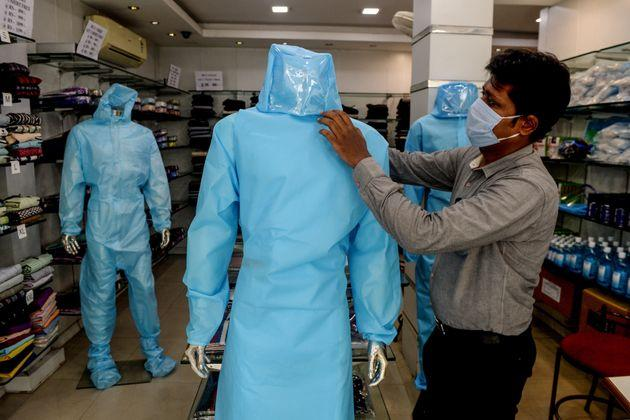 A shopkeeper arranges a protective suit for sale on a mannequin at a garment shop after the government eased a nationwide lockdown, in Chennai on May 28, 2020.