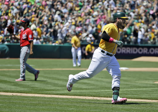 Oakland Athletics' Derek Norris, right, runs down the first base line after his second three-run home run of a baseball game against Washington Nationals pitcher Gio Gonzalez, left, during the second inning on Sunday, May 11, 2014, in Oakland, Calif. (AP Photo/Marcio Jose Sanchez)