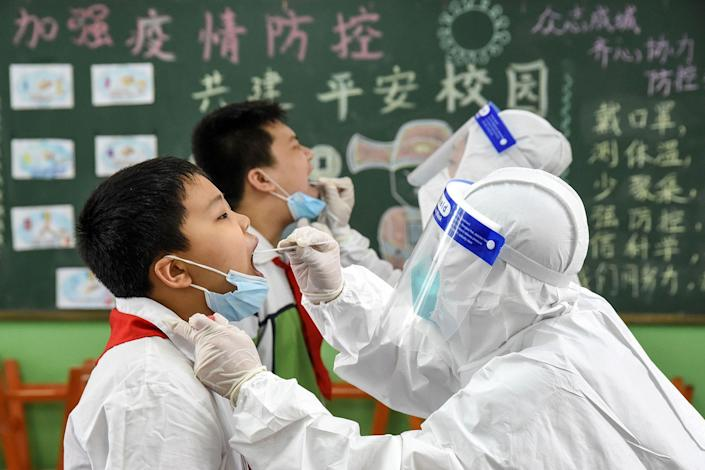 This photograph taken on August 17, 2020 shows a medical worker taking a swab sample from an elementary school student, to be tested for the COVID-19 coronavirus before schools open for the new semester, in Handan in China's northern Hebei province.