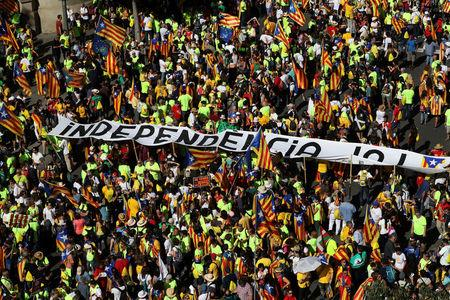 """A man carries a sign that reads """"Spain for sale"""" next to a huge banner reading """"Independence Now"""" during a rally on Catalonia's national day 'La Diada' in Barcelona, Spain, September 11, 2017. REUTERS/Susana Vera"""