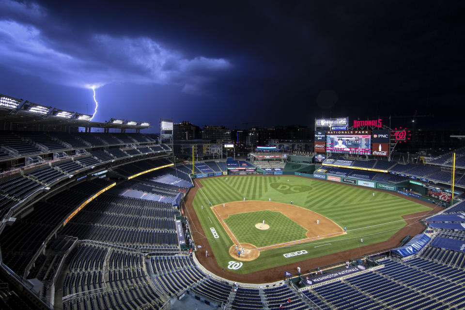 A bolt of lightning comes down from the clouds during the sixth inning of an opening day baseball game between the Washington Nationals and the New York Yankees at Nationals Park, Thursday, July 23, 2020, in Washington. (AP Photo/Alex Brandon)