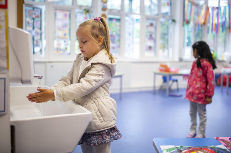 LONDON, ENGLAND - JUNE 10: A child maintains social distancing measures while washing hands ahead of a lesson at Earlham Primary School, which is part of the Eko Trust on June 10, 2020 in London, England. As part of Covid-19 lockdown measures, Earlham Primary School is teaching smaller 'bubbles' of students, to help maintain social distancing measures. School staff have put into place many safety measures such as corridor signage for a one way system, regular supervised handwashing, temperature checks on arrival and enhanced cleaning regimes to keep pupils and staff as safe as possible. Bubbles of pupils are limited to six and each have their own well-ventilated space. The Government have announced it is set to drop plans for all English primary pupils to return to school before the end of the summer. (Photo by Justin Setterfield/Getty Images)