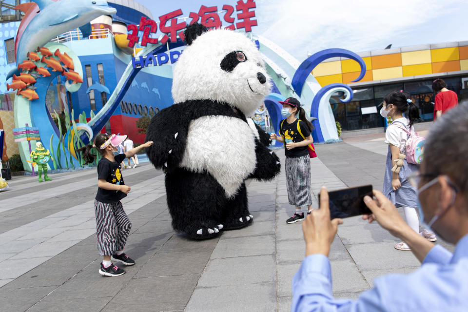 In this, Tuesday, May 19, 2020, photo released by Xinhua News Agency, tourists wearing mask sas precaution against the coronavirus pose for photos with a panda mascot at the Happy Valley Wuhan theme park in Wuhan, in central China's Hubei Province, Happy Valley Wuhan, a theme park which had been closed due to the COVID-19 outbreak, has partly reopened on Tuesday with limitation on numbers and requiring online pre-booking. (Xiong Qi/Xinhua via AP)