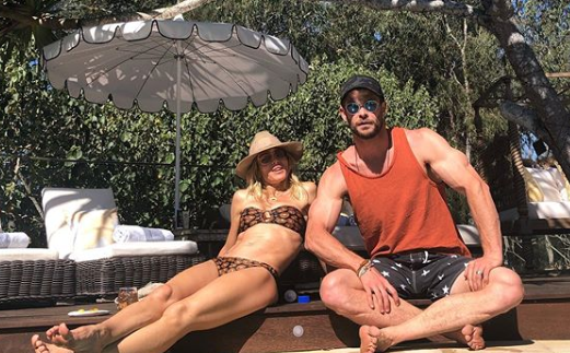 A photo of Elsa Pataky wearing a bikini and Chris Hemsworth wearing an orange singlet on a wooden deck.