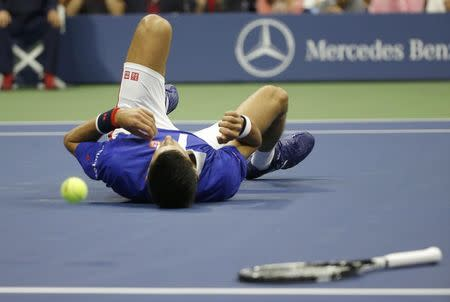 Novak Djokovic of Serbia falls to the court while trying to return a shot from Roger Federer of Switzerland in the first set during their men's singles final match at the U.S. Open Championships tennis tournament in New York, September 13, 2015. REUTERS/Mike Segar