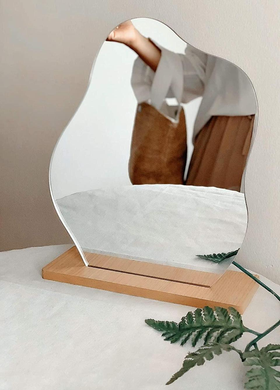 """<h3>Frameless Cloud-Shaped Mirror & Stand</h3><br>Complete the aforementioned dreamy vanity setup with this wavy cloud-shaped gem. <br><br><strong>All Things Shared</strong> Frameless Cloud-Shaped Mirror & Stand, $, available at <a href=""""https://amzn.to/3bERwJz"""" rel=""""nofollow noopener"""" target=""""_blank"""" data-ylk=""""slk:Amazon"""" class=""""link rapid-noclick-resp"""">Amazon</a>"""