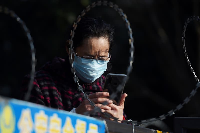 FILE PHOTO: A woman uses her mobile phone behind barbed wire at an entrance of a residential compound in Wuhan