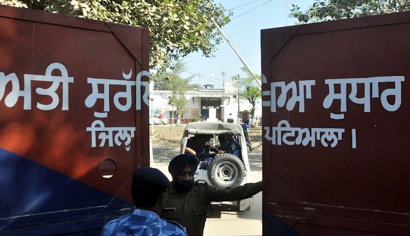 An Indian police official stands at the gate of the Nabha maximum-security jail in Nabha in the northern state of Punjab on November 27, 2016 following an attack by at least 10 armed men disguised as policemen (AFP Photo/)