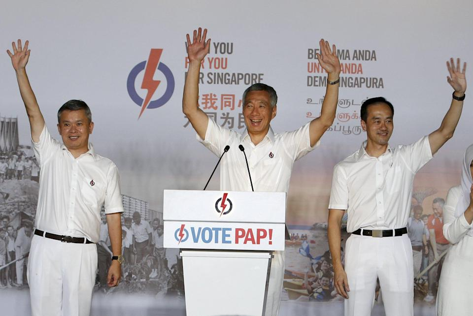 Singapore's Prime Minister and Secretary-General of the People's Action Party Lee Hsien Loong (C) thanks supporters with his team after the general election results at a stadium in Singapore September 12, 2015. Singapore's ruling party romped to a strong election victory on Friday and was on course to increase its share of the vote and seat tally as it brushed off an opposition challenge in the city state's most hotly contested polls. REUTERS/Edgar Su
