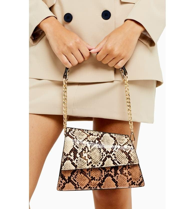 "<p>We love the asymmetrical design of this <a href=""https://www.popsugar.com/buy/Topshop-Star-Snakeskin-Print-Shoulder-Bag-490029?p_name=Topshop%20Star%20Snakeskin%20Print%20Shoulder%20Bag&retailer=shop.nordstrom.com&pid=490029&price=40&evar1=fab%3Aus&evar9=45639990&evar98=https%3A%2F%2Fwww.popsugar.com%2Ffashion%2Fphoto-gallery%2F45639990%2Fimage%2F46609236%2FTopshop-Star-Snakeskin-Print-Shoulder-Bag&list1=shopping%2Cfall%20fashion%2Cbags%2Cpurses%2Cwinter%20fashion&prop13=mobile&pdata=1"" rel=""nofollow"" data-shoppable-link=""1"" target=""_blank"" class=""ga-track"" data-ga-category=""Related"" data-ga-label=""https://shop.nordstrom.com/s/topshop-star-snakeskin-print-shoulder-bag/5424620?origin=category-personalizedsort&amp;breadcrumb=Home%2FWomen%2FHandbags&amp;color=brown%20multi"" data-ga-action=""In-Line Links"">Topshop Star Snakeskin Print Shoulder Bag </a> ($40).</p>"