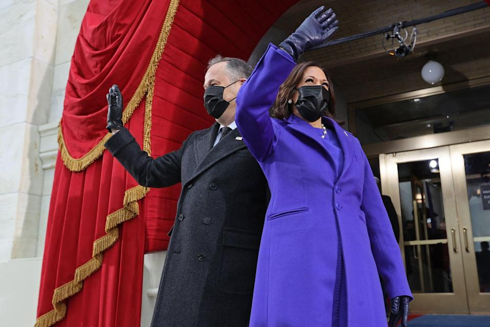 US Vice President-elect Kamala Harris (R) and US Second Gentleman Doug Emhoff wave as they arrive for the inauguration of Joe Biden as the 46th US President, on the West Front of the US Capitol in Washington, DC on January 20, 2021. (Photo by JONATHAN ERNST / POOL / AFP) (Photo by JONATHAN ERNST/POOL/AFP via Getty Images)