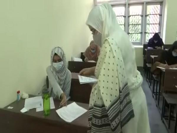 An invigilator hands out the question paper for the entrance exam at SKUAST. (Photo/ANI)