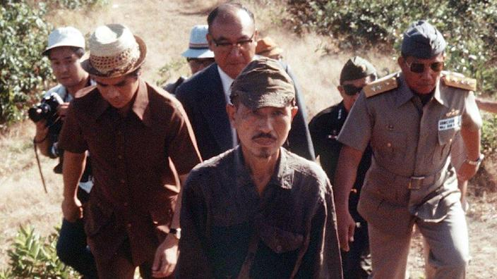 Lieutenant Hiroo Onoda (centre) walks from the jungle in 1974