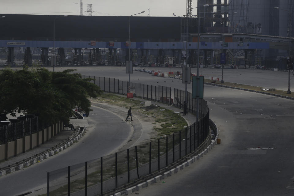 A Police officer crosses a road in front of the Lekki toll gate in Lagos, Nigeria, Wednesday Oct. 21, 2020. After 13 days of protests against alleged police brutality, authorities have imposed a 24-hour curfew in Lagos, Nigeria's largest city, as moves are made to stop growing violence. ( AP Photo/Sunday Alamba)
