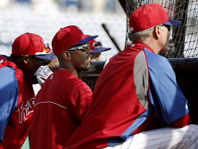 Philadelphia Phillies' Jimmy Rollins, center, talks with manager Ryne Sandberg, right, as they watch batting practice before a spring exhibition baseball game against the Toronto Blue Jays in Clearwater, Fla., Thursday, March 20, 2014. (AP Photo/Kathy Willens)