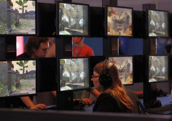 Visitors play 'World of Warcraft' at an exhibition stand during the Gamescom 2012 fair in Cologne August 15, 2012.