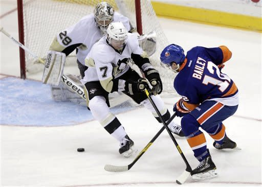 New York Islanders' Josh Bailey, right, passes around Pittsburgh Penguins' Paul Martin, center, and Marc-Andre Fleury to teammate Kyle Okposo, not pictured, who would score on the play during the third period of an NHL hockey game, Thursday, March 29, 2012, in Uniondale, N.Y. The Islanders won 5-3. (AP Photo/Seth Wenig)