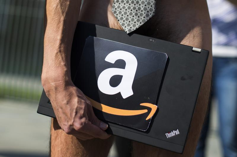 Man holds laptop with logo of online retailer Amazon during protest in Berlin demanding implementation of unitary tax to fight tax evasion
