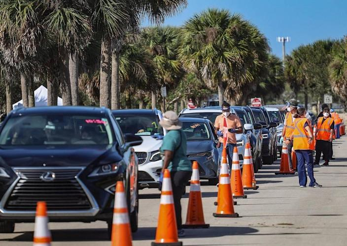 On Sunday, January 3, 2021 motorists line-up for COVID-19 vaccination shots for people who are 65 and older as site staffers assist at Vista View Park in Davie, Florida.