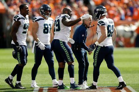 FILE PHOTO: Sep 9, 2018; Denver, CO, USA; Seattle Seahawks head coach Pete Carroll reacts with tight end Will Dissly (88) and defensive tackle Quinton Jefferson (99) and tight end Nick Vannett (81) and defensive end Dion Jordan (95) in the first quarter against the Denver Broncos at Broncos Stadium at Mile High. Mandatory Credit: Isaiah J. Downing-USA TODAY Sports/File Photo