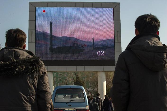 People watch news footage of a missile launch on a giant TV screen outside the main railway station in Pyongyang, on March 7, 2017 (AFP Photo/Kim Won-Jin)