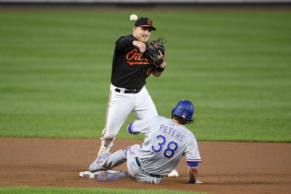 Texas Rangers' DJ Peters (38) is out at second as Baltimore Orioles second baseman Pat Valaika (11) throws to first to put out Jonah Heim for a double-play during the fourth inning of a baseball game, Friday, Sept. 24, 2021, in Baltimore. (AP Photo/Nick Wass)