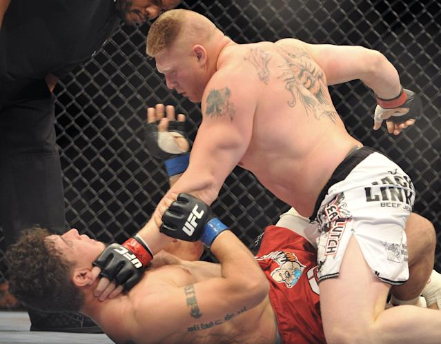 Brock Lesnar (top) puts the finishing touches on Frank Mir in their heavyweight title bout at UFC 100. (Getty Images)