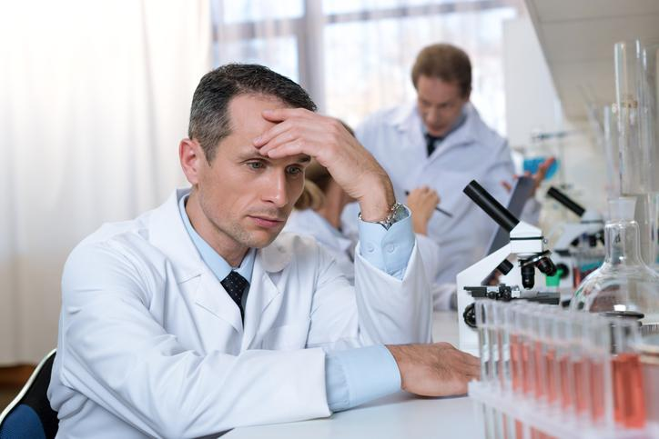 A scientist in a lab with a disappointed look on his face.
