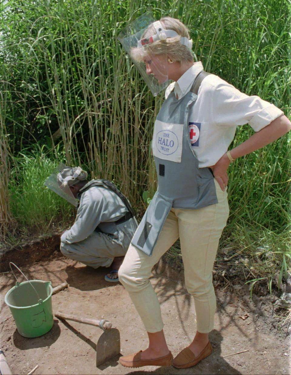 """FILE - In this Jan. 15, 1997 file photo, Diana, Princess of Wales, wearing protective gear, watches a land-mine clearing demonstration in Huambo, central Angola, one of the most densely mined areas in the country. For someone who began her life in the spotlight as """"Shy Di,"""" Princess Diana became an unlikely, revolutionary during her years in the House of Windsor. She helped modernize the monarchy by making it more personal, changing the way the royal family related to people. By interacting more intimately with the public -- kneeling to the level of children, sitting on edge of a patient's hospital bed, writing personal notes to her fans -- she set an example that has been followed by other royals as the monarchy worked to become more human and remain relevant in the 21st century. (AP Photo/Giovanni Diffidenti, File)"""