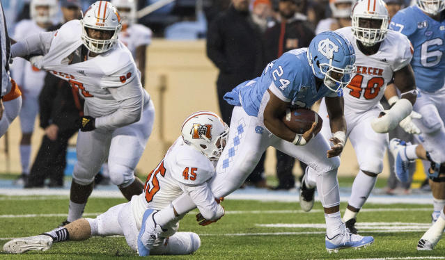 North Carolina's Antonio Williams (24) carries the ball as Mercer's Andrew Pettit (45) attempts a tackle during the first half of an NCAA college football game in Chapel Hill, N.C., Saturday, Nov. 23, 2019. (AP Photo/Ben McKeown)