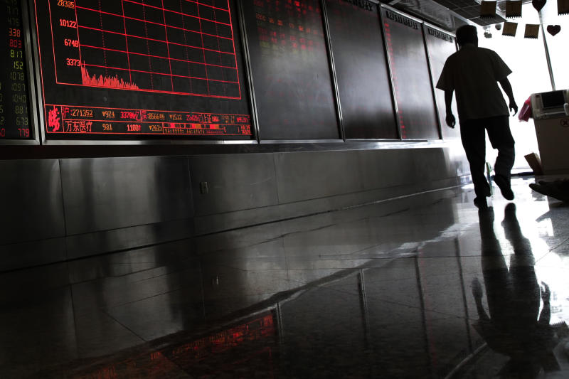 A man walks by an electronic board displaying stock prices at a brokerage house in Beijing, Thursday, Aug. 16, 2018. Asian shares are falling as investors fret over slowing economic growth, especially in China. Technology stocks and oil and metals prices skidded overnight on Wall Street. (AP Photo/Andy Wong)