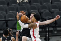 San Antonio Spurs center Jakob Poeltl, center left, and Houston Rockets forward Kenyon Martin Jr., right, scramble for a rebound during the first half of an NBA basketball game in San Antonio, Thursday, Jan. 14, 2021. (AP Photo/Eric Gay)