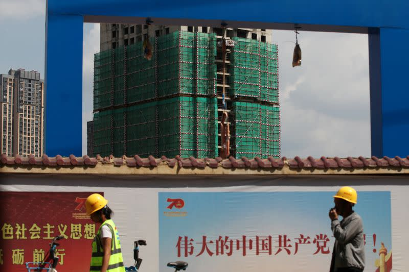 Workers walk past a construction site of residential buildings by property developer Country Garden in Kunming, Yunnan