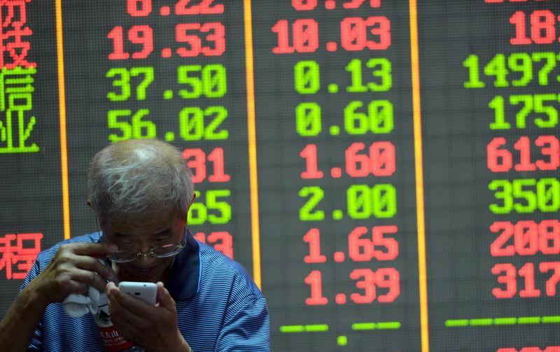 An investor checks on his mobile phone in front of an electronic board showing stock information at a brokerage house in Hangzhou