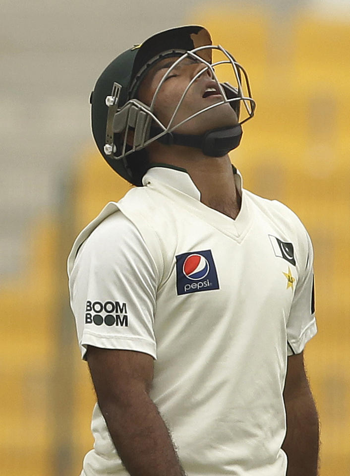 Pakistan's Asad Shafiq walks off the field of play after losing his wicket to England's Monty Panesar during the fourth day of the second cricket test match of a three-match series between England and Pakistan at Zayed Cricket Stadium in Abu Dhabi, United Arab Emirates, Saturday, Jan. 28, 2012. (AP Photo/Hassan Ammar)
