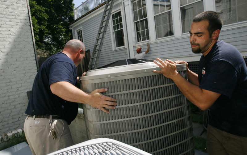 FILE- In this Monday June 9, 2008, file photo, Charles Brinkley, left, and John Lerro, with Great American Heating and Air Conditioning, Inc., install an air conditioner in Chevy Chase, Md. A sharp decline in the price of natural gas makes it much cheaper for U.S. utilities to produce electricity. It just isn't having any impact on homeowners' monthly bills. Instead of falling, electricity prices aren't budging. They are rising just as families begin cranking up their air conditioners. (AP Photo/Jacquelyn Martin, File)