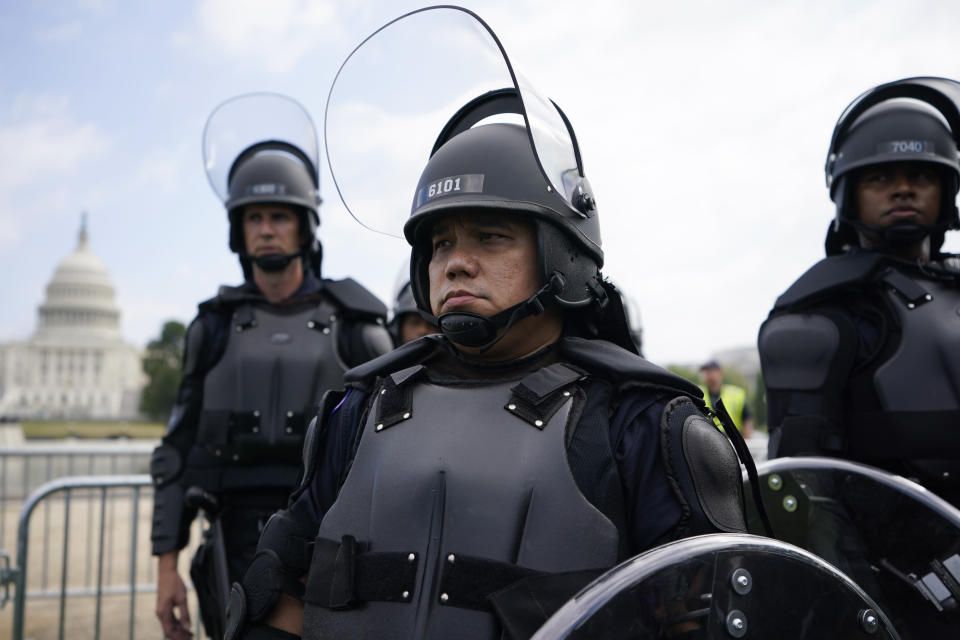 """Police in riot gear patrol as people attend a rally near the U.S. Capitol in Washington, Saturday, Sept. 18, 2021. The rally was planned by allies of former President Donald Trump and aimed at supporting the so-called """"political prisoners"""" of the Jan. 6 insurrection at the U.S. Capitol. (AP Photo/Brynn Anderson)"""
