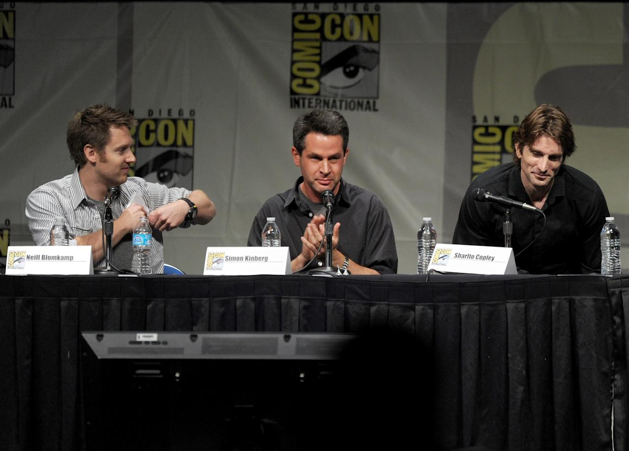 """SAN DIEGO, CA - JULY 13:  (L-R) Director Neill Blomkamp, producer Simon Kinberg, and actor Sharlto Copley speak during Sony's """"Eylsium"""" panel during Comic-Con International 2012 at San Diego Convention Center on July 13, 2012 in San Diego, California.  (Photo by Kevin Winter/Getty Images)"""