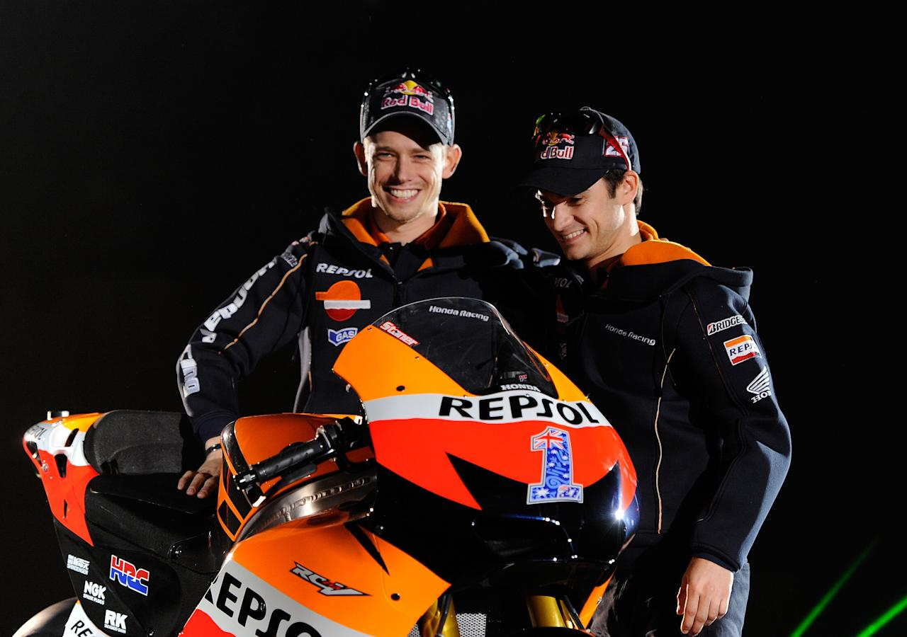 Australian  MotoGP rider Casey Stoner (L) and Spanish MotoGP rider Dani Pedrosa wave to fans on March 3, 2012 during the presentation of the Repsol Honda Team 2012 at the Sports Palace in Madrid.                  AFP PHOTO/Dani POZO (Photo credit should read DANI POZO/AFP/Getty Images)