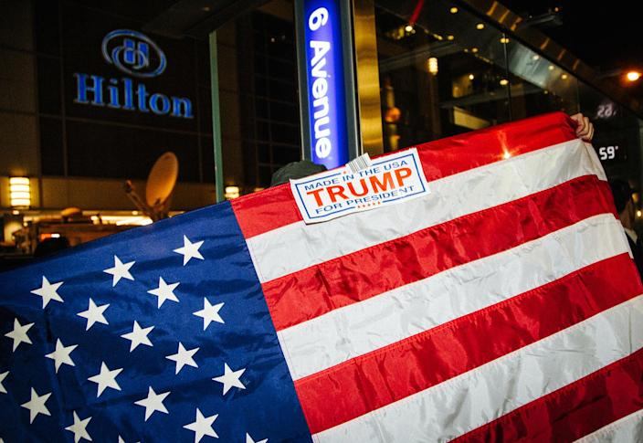 <p>A supporter of Republican Donald Trump celebrates with a flag outside Hilton Midtown, New York, Nov. 9, 2016.. Americans voted on Election Day to choose the 45th President of the United States of America to serve from 2017 through 2020. Nov. 9, 2016. (Photo: ALBA VIGARAY/EPA) </p>