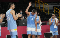 Argentina's Luis Scola (4) waves as he receives an emotional standing ovation from his team, Australia players, and others in attendance when he was pulled from the game in the final moments of a men's basketball quarterfinal round game at the 2020 Summer Olympics, Tuesday, Aug. 3, 2021, in Saitama, Japan. (AP Photo/Eric Gay)