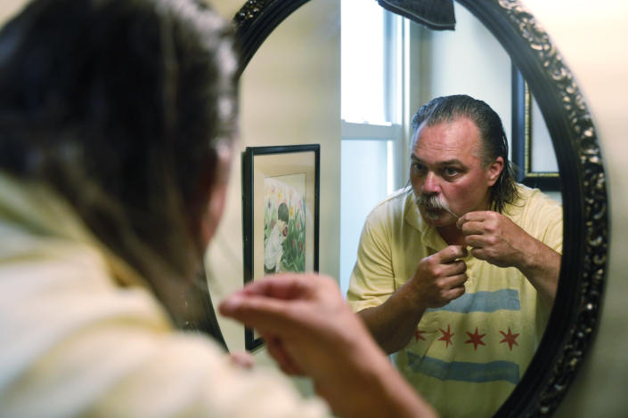 Dan O'Connor styles his mustache before exiting his house for his 365th plunge into Lake Michigan, Saturday, June 12, 2021, in Chicago's Lincoln Park. (AP Photo/Shafkat Anowar)