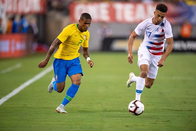 Antonee Robinson (right) got beat on this play by Brazil's Douglas Costa, but Robinson looks like he could be the USA's starting left back for many years to come. (EFE/EPA/COREY SIPKIN)