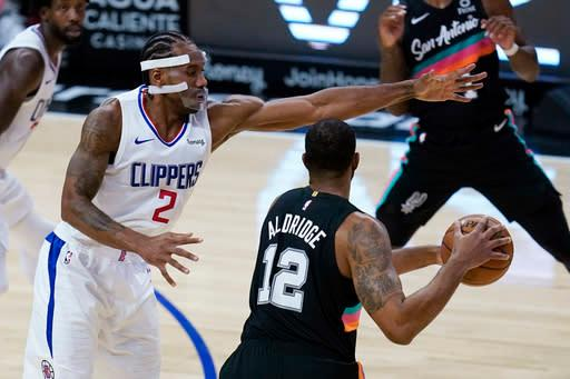 Los Angeles Clippers forward Kawhi Leonard, left, defends against San Antonio Spurs forward LaMarcus Aldridge (12) during the second quarter of an NBA basketball game Tuesday, Jan. 5, 2021, in Los Angeles. (AP Photo/Ashley Landis)
