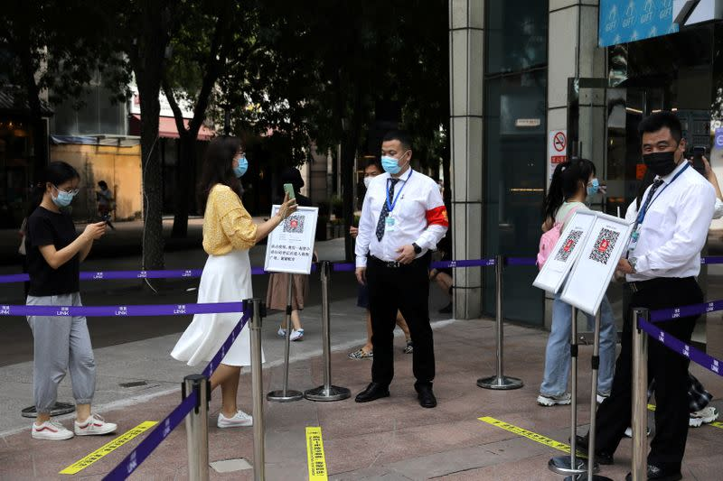 FILE PHOTO: Woman shows her health status on a phone to a security guard, at an entrance of a shopping mall in Beijing