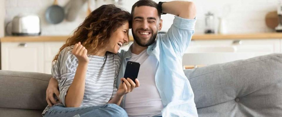 Cheerful married couple resting on couch looking at phone